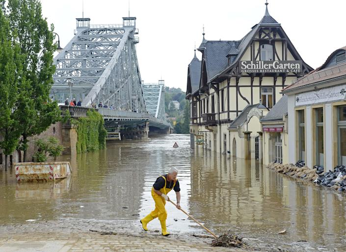 A helper cleans the bank of river Elbe in front of the historical bridge Blaues Wunder (Blue Miracle), left, in Dresden, eastern Germany, Thursday, June 6, 2013. The Bridge was closed for the car traffic. Heavy rainfalls cause flooding along rivers and lakes in Germany, Austria, Switzerland and the Czech Republic. (AP Photo/Jens Meyer)