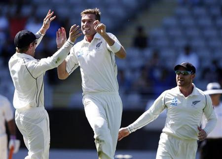 New Zealand's Tim Southee celebrates dismissing Rohit Sharma with teammates Kane Willamson (L) and Brendon McCullum (R) during the second innings on day four of the first international test cricket match at Eden Park in Auckland, February 9, 2014. REUTERS/Nigel Marple