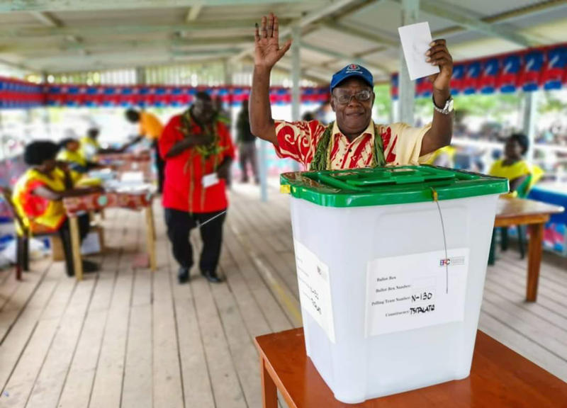 A man raises his hands as he prepares to cast a vote in Buka, the Autonomous Region of Bougainville, Papua New Guinea, Saturday, Nov. 23, 2019, in a historic referendum to decide if they want to become the world's newest nation by gaining independence from Papua New Guinea. (Post Courier via AP)