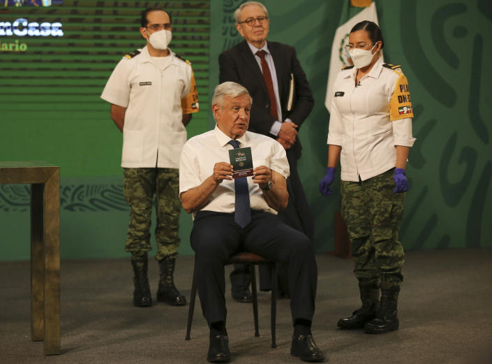 Mexican President Andres Manuel Lopez Obrador shows his vaccination certificate after getting a shot of the AstraZeneca vaccine for COVID-19 during his daily, morning news conference at the presidential palace in Mexico City, Tuesday, April 20, 2021. (AP Photo/Fernando Llano)