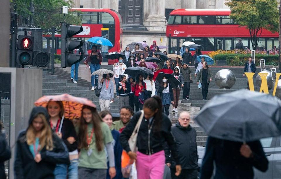 People shelter from the rain under umbrellas  near St Paul's Cathedral  (PA)