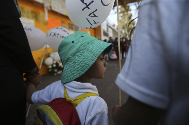 A child, student of the Enrique C. Rebsamen primary school, walks in the funeral procession of 7-year-old murder victim Fatima, accompanied by his parents in Mexico City, Tuesday, Feb. 18, 2020. Fatima was abducted from the door of the primary school and her body was found wrapped in a bag and abandoned in a rural area on Saturday. Five people have been questioned in the case and video footage of her abduction exists. (AP Photo/Marco Ugarte)
