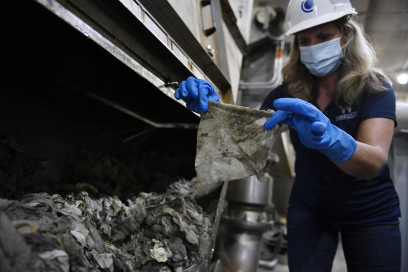 "In this May 28, 2020, file photo Lyn Riggins, WSSC Water spokesperson, holds up a wipe that was collected along with other debris at a pumping station in Washington. Sewer systems are battling the ""wipe monster"" from all the wipes and other debris since pandemic that are clogging up pumping stations. (AP Photo/Susan Walsh)"
