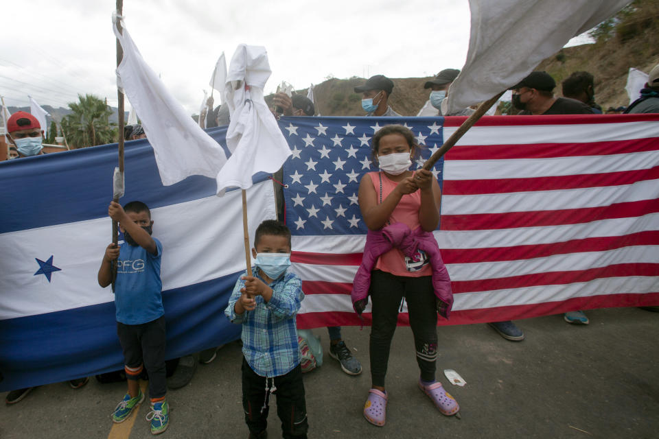 Honduran migrant children raise white flags in front of a Honduran and American flag, as they are blocked by Guatemalan soldiers and police from advancing toward the U.S.-Mexico border, on the highway in Vado Hondo, Guatemala, Monday, Jan. 18, 2021. Some migrants have expressed hope about a friendlier reception from the new U.S. administration. (AP Photo/Sandra Sebastian)