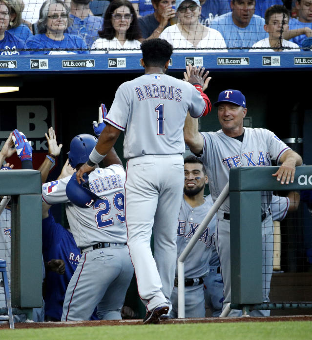 Texas Rangers' Elvis Andrus (1) celebrates with manager Jeff Banister, right, as he comes into the dugout after scoring on a three-run home run by Adrian Beltre during the third inning of a baseball game against the Kansas City Royals Monday, June 18, 2018, in Kansas City, Mo. (AP Photo/Charlie Riedel)