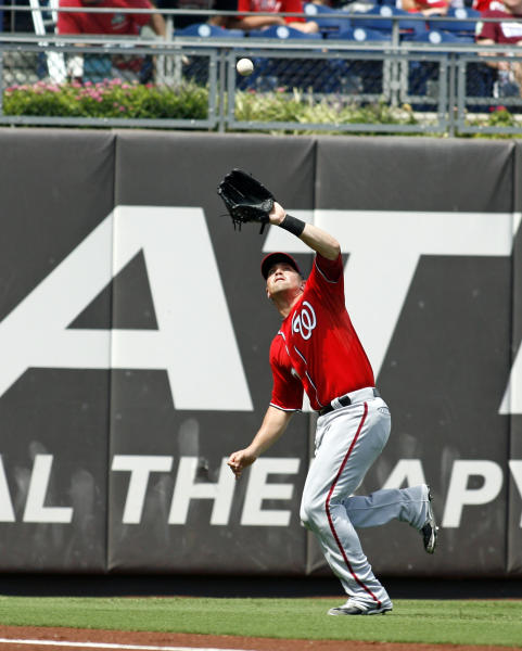 Washington Nationals' Tyler Moore fields a fly ball hit by Philadelphia Phillies' Laynce Nix for an out in the second inning of a baseball game on Sunday, Aug. 26, 2012, in Philadelphia. (AP Photo/H. Rumph Jr)