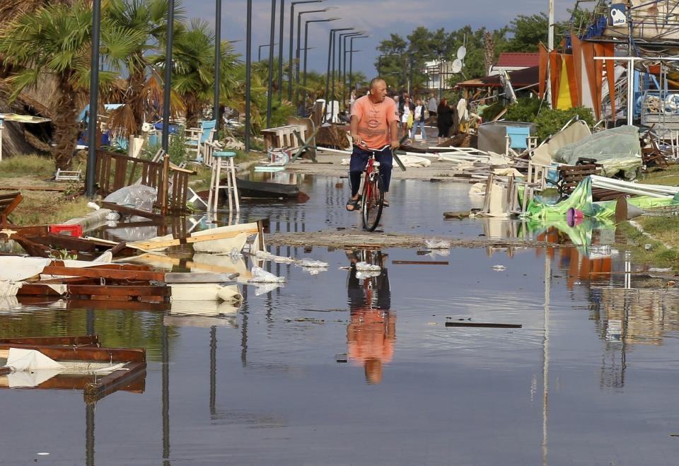 A man rides a bicycle among debris after a storm at Nea Plagia village in Halkidiki region, northern Greece, Thursday, July 11, 2019. A powerful storm hit the northern Halkidiki region late Wednesday. (Giannis Moisiadis/InTime News via AP) (Giannis Moisiadis/InTime News via AP)