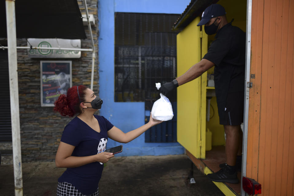 FILE - In this May 21, 2020 file photo, Yamirka Marmolejos, owner of a pet grooming business that has been closed since the start of the COVID-19 lockdown, takes a food order from Alfredo Gonzalez, both wearing masks as a precaution against the spread of the coronavirus, in Canovanas, Puerto Rico. More than 30,000 jobs have been lost because of the new coronavirus outbreak, and at least 1,400 businesses have closed. (AP Photo/Carlos Giusti, File)