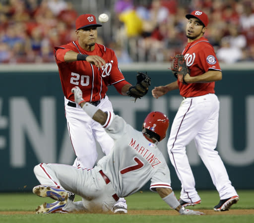 Washington Nationals shortstop Ian Desmond (20) gets the out at second on Philadelphia Phillies' Michael Martinez (7) with second baseman Anthony Rendon at right, as he completes the double play during the fourth inning of a baseball game at Nationals Park, Saturday, Aug. 10, 2013, in Washington. (AP Photo/Alex Brandon)