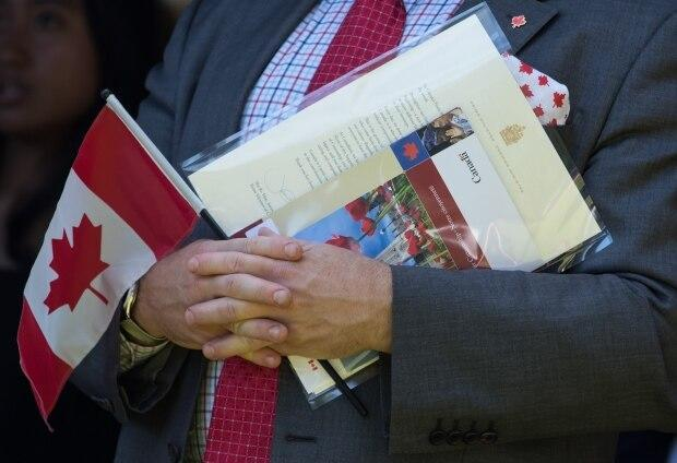 A new Canadian holds a Canadian flag, their citizenship certificate and a letter signed by Prime Minister Justin Trudeau as they sing O Canada after becoming a Canadian citizen, during a Canada Day citizenship ceremony in West Vancouver on Monday, July 1, 2019. (Darryl Dyck/The Canadian Press - image credit)