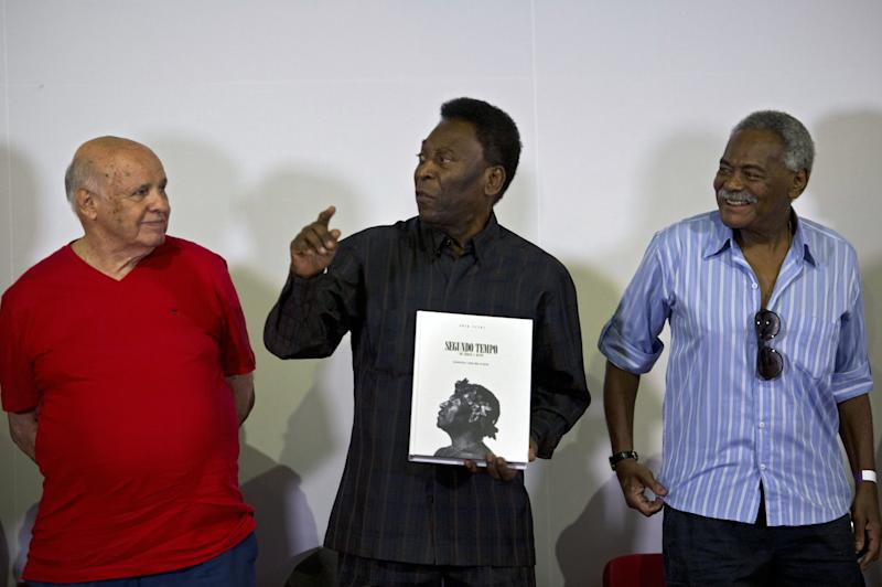 "Brazilian football legend Edson Arantes do Nascimento, known as ""Pele"" (C), speaks next to former teammates Pepe (L) and Coutinho (R), during the autograph ceremony of his book ""Segundo Tempo"" (Second Half), in Santos, some 70 km from Sao Paulo, Brazil, on March 12, 2015. AFP PHOTO / NELSON ALMEIDA (Photo credit should read NELSON ALMEIDA/AFP/Getty Images)"
