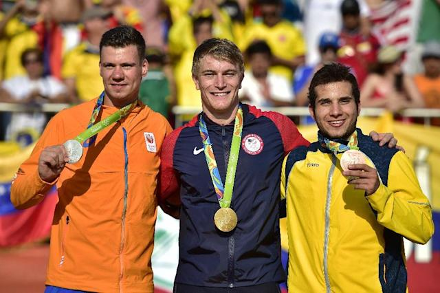 Netherlands' Jelle Van Gorkom (L), US Connor Fields (C) and Colombia's Carlos Alberto Ramirez Yepes (R) celebrate on the podium of the men's BMX cycling event of the Rio 2016 Olympic Games August 19, 2016 (AFP Photo/CARL DE SOUZA )