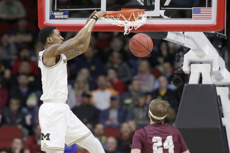 Michigan's Charles Matthews, left, dunks over Montana's Bobby Moorehead (24) during the first half of a first round men's college basketball game in the NCAA Tournament in Des Moines, Iowa, Thursday, March 21, 2019. (AP Photo/Nati Harnik)