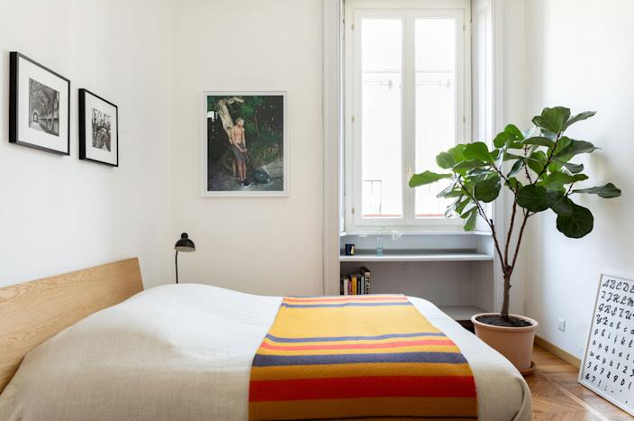 """<div class=""""caption""""> The guest bedroom mirrors Alex's, with the same Muji bed topped by an Hermès blanket—this time in a striking orange colorway. A chromogenic print by <a href=""""http://www.thomashumery.com/"""" rel=""""nofollow noopener"""" target=""""_blank"""" data-ylk=""""slk:Thomas Humery"""" class=""""link rapid-noclick-resp"""">Thomas Humery</a> hangs on the wall beside the window and a poster by <a href=""""https://www.artsy.net/artist/rayyane-tabet"""" rel=""""nofollow noopener"""" target=""""_blank"""" data-ylk=""""slk:Rayyane Tabet"""" class=""""link rapid-noclick-resp"""">Rayyane Tabet</a> is casually propped on the floor. </div>"""