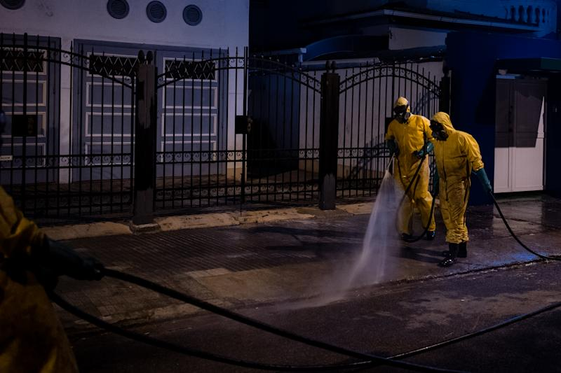 Workers spray desinfecting agent on the sidewalks in Boqueirão neighborhood as a way to combat coronavirus (COVID-19) transmission during the night in Santos, Brazil, April 25, 2020. (Photo by Felipe Beltrame/NurPhoto via Getty Images)