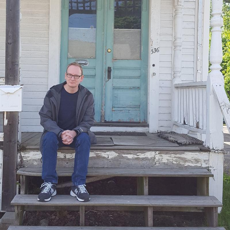 Michael Broussard in 2017 on the porch of the house on High Street in Clinton, Massachusetts, where he lived while being assaulted by his stepfather. (Kristie Kozenewski)