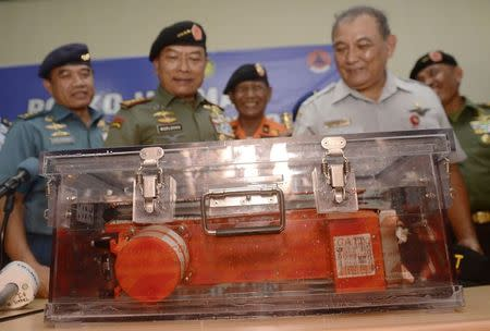 Tatang Kurniadi (R), head of the National Transportation Safety Committee, and Indonesian Armed Forces Chief Moeldoko (2nd L) present the flight data recorder from AirAsia QZ8501 to the media at the airbase in Pangkalan Bun, Central Kalimantan January 12, 2015, in this photo taken by Antara Foto. REUTERS/Antara Foto/Prasetyo Utomo