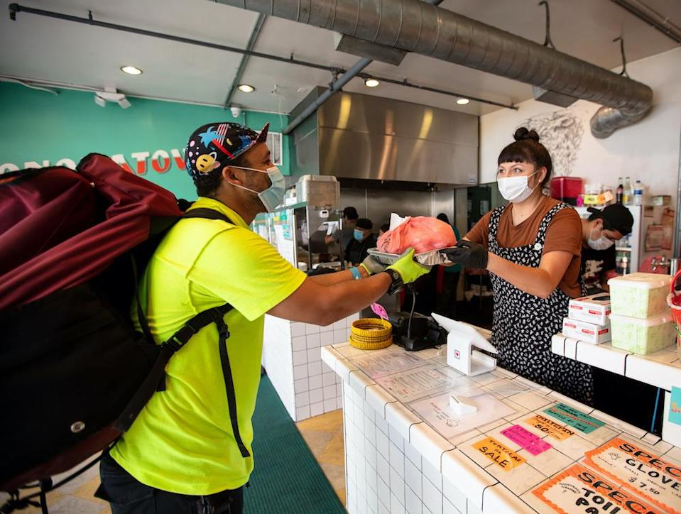 A Mexican restaurant adapts to the Covid-19 lockdown. A delivery cyclist wearing a massive backpack takes an order from behind the counter. Everyone is wearing masks and gloves.