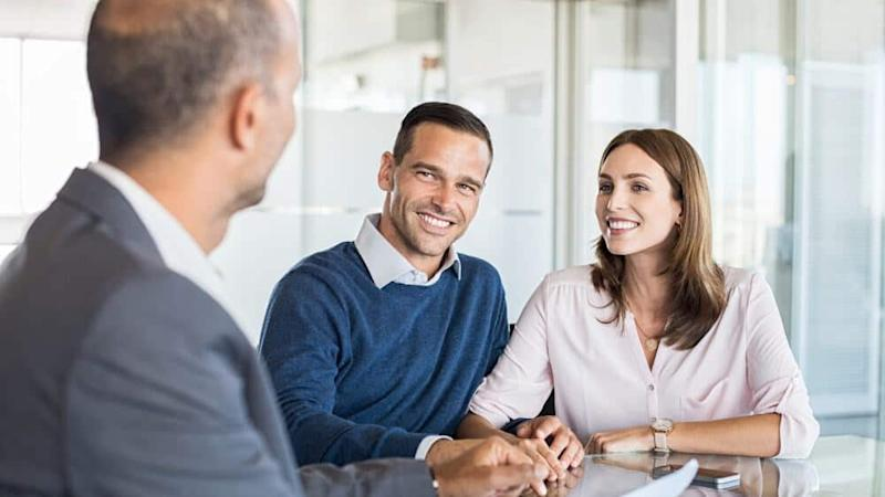 Mature financial advisor showing report to young couple for their investment