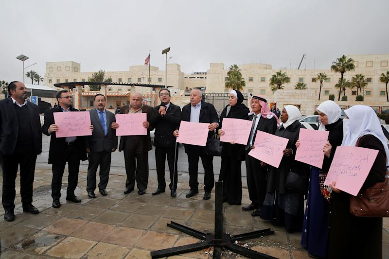 Jordanian members of Parliament hold signs during a sit-in against Trump's decision in front of the U.S. Embassy in Amman, Jordan, December 6, 2017.