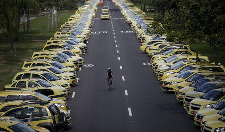 A man rides his bicycle between taxis parked on the street during a protest against the online car-sharing service Uber in Rio de Janeiro, Brazil July 24, 2015. REUTERS/Ricardo Moraes      TPX IMAGES OF THE DAY