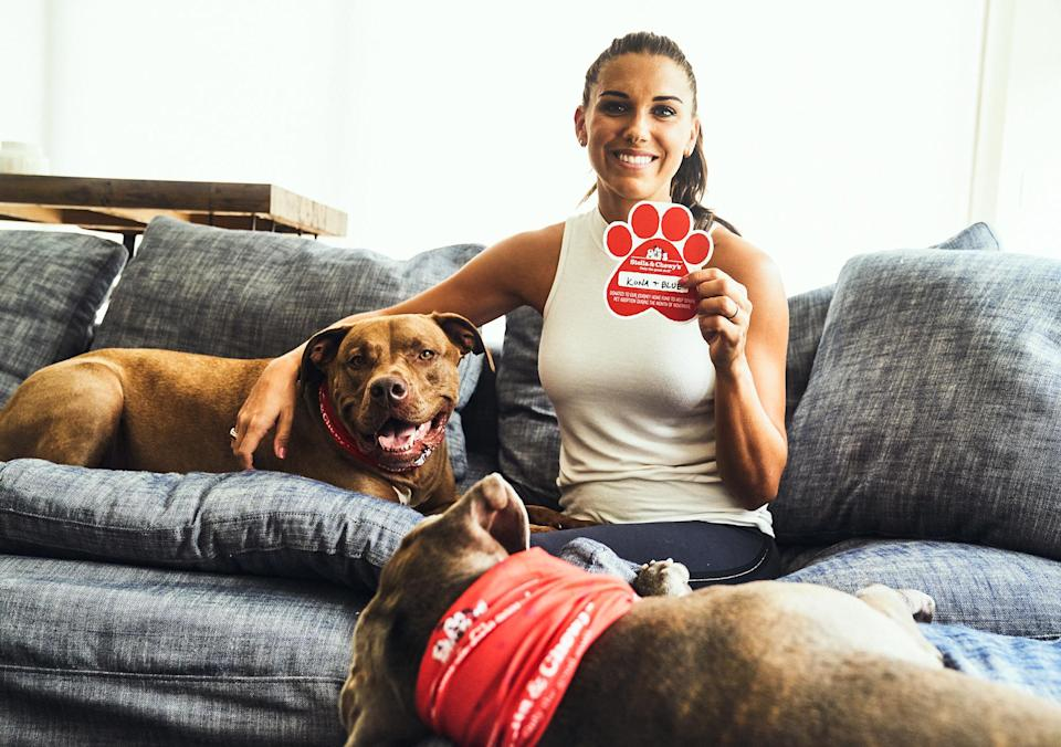 <p>Alex Morgan poses with her rescue dogs and a paw print that she signed in honor of them for Stella and Chewy's National Adopt a Senior Pet Month Program on Wednesday. </p>