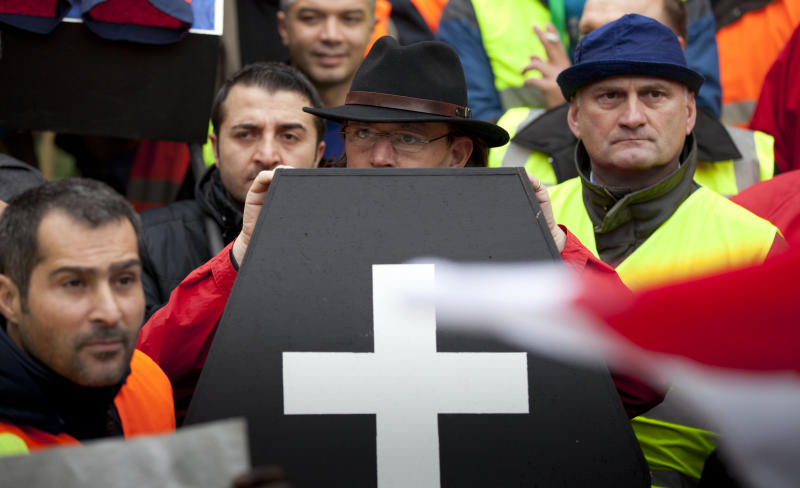 Airport ground workers and baggage handlers demonstrate with a mock coffin in front of EU headquarters in Brussels on Monday, Nov. 5, 2102. Workers are protesting against a proposal for more competition in the market which they feel will  have a negative effect on their working conditions. (AP Photo/Virginia Mayo)