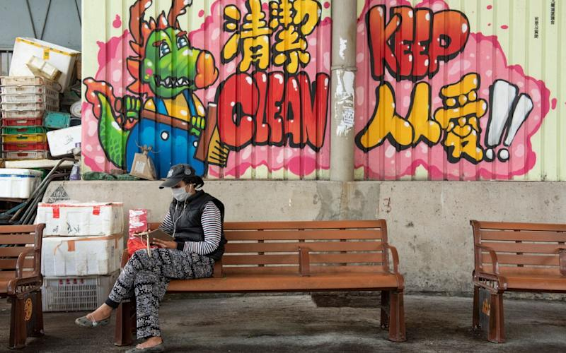 A woman wears a face mask as she sits on a bench in Hong Kong - Rex