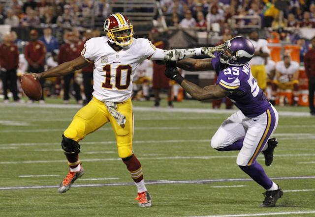 Washington Redskins quarterback Robert Griffin III, left, tries to break away from Minnesota Vikings outside linebacker Marvin Mitchell during the first half of an NFL football game Thursday, Nov. 7, 2013, in Minneapolis. (AP Photo/Ann Heisenfelt)