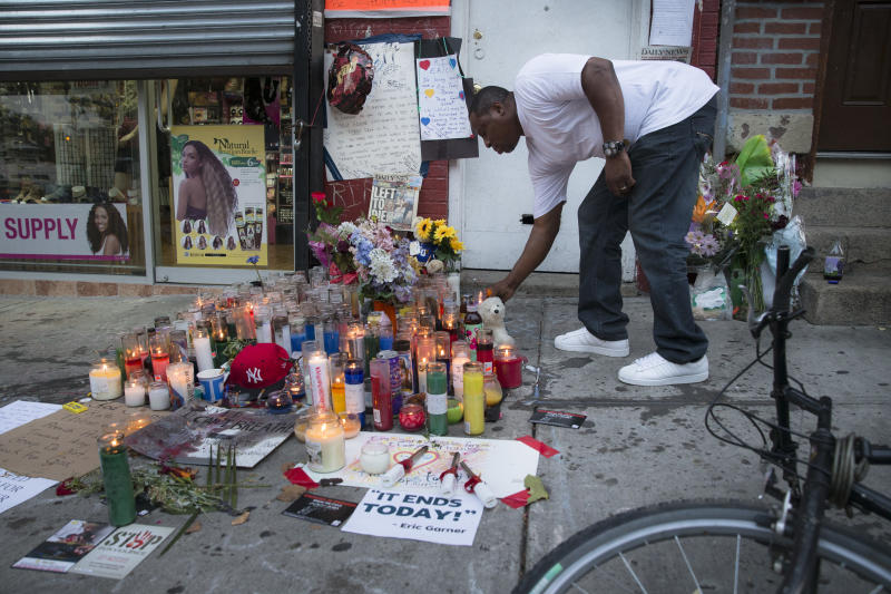 A mourner places a candle at a memorial for Eric Garner, a Staten Island man who died while being arrested by New York City police. (Photo: John Minchillo/AP)