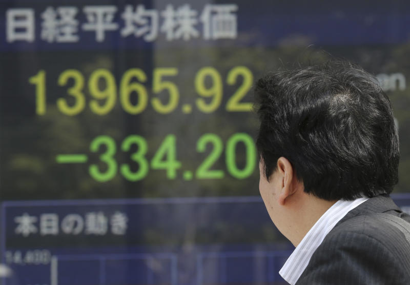A man looks at an electronic stock board of a securities firm in Tokyo, Friday, April 11, 2014. Tokyo's Nikkei 225 stock average fell more than 400 points at one point in morning trading. (AP Photo/Koji Sasahara)