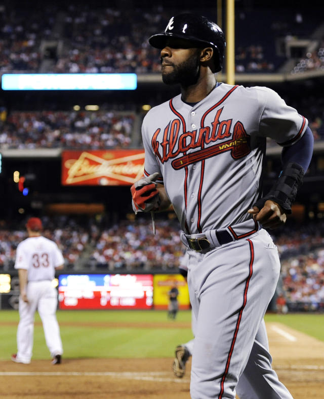 Philadelphia Phillies' Cliff Lee walks back to the pitchers mound as Atlanta Braves' Jason Heyward walks to the dugout after scoring on a Justin Upton double in the fourth inning of a baseball game on Sunday, Aug. 4, 2013, in Philadelphia. (AP Photo/Michael Perez)
