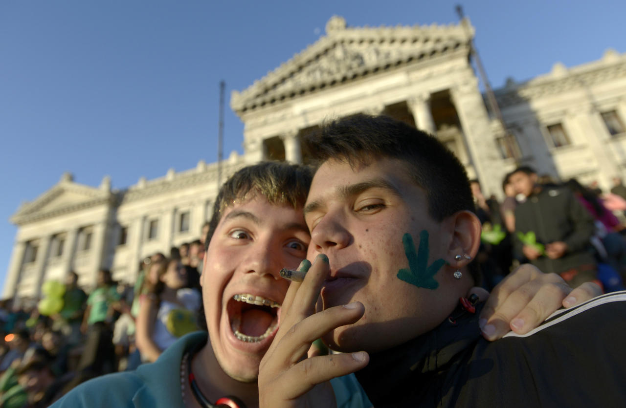 An activist smokes a marijuana cigarette as they poses for photos in front of the Congress in Montevideo, Uruguay, Tuesday, Dec. 10, 2013. Uruguay's Senate approved the world's first national marketplace for legal marijuana Tuesday, an experiment that puts the government in charge of growing, selling and using a drug that is illegal almost everywhere else. (AP Photo/Matilde Campodonico)