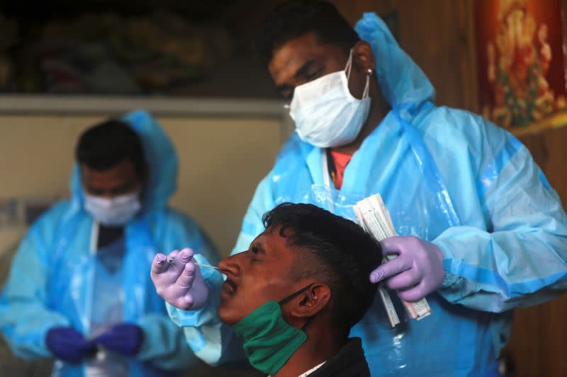 Health worker collects a swab sample from a man during a rapid antigen testing campaign, on the outskirts of Mumbai
