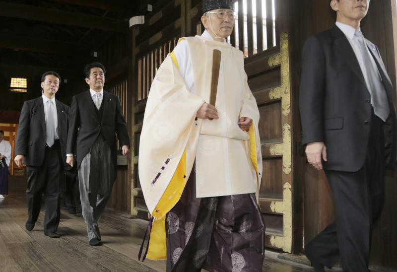"""Japanese Prime Minister Shinzo Abe, second from left, follows a Shinto priest to pay respect for the war dead at Yasukuni Shrine in Tokyo Thursday, Dec. 26, 2013. Abe visited Yasukuni war shrine in a move sure to infuriate China and South Korea. The visit to the shrine, which honors 2.5 million war dead including convicted class A war criminals, appears to be a departure from Abe's """"pragmatic"""" approach to foreign policy, in which he tried to avoid alienating neighboring countries. It was the first visit by a sitting prime minister since Junichiro Koizumi went to mark the end of World War II in 2006. (AP Photo/Shizuo Kambayashi)"""