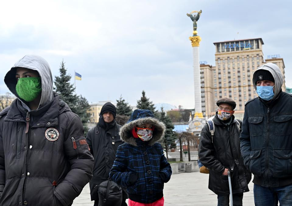 Homeless and vulnerable people wearing face masks, amid concerns over the spread of the novel coronavirus COVID-19, keep their distance from each other while queuing to get free meals distributed by charity activists at the Independence Square in the capital of Kiev on April 1, 2020. (Photo by Sergei SUPINSKY / AFP) (Photo by SERGEI SUPINSKY/AFP via Getty Images)