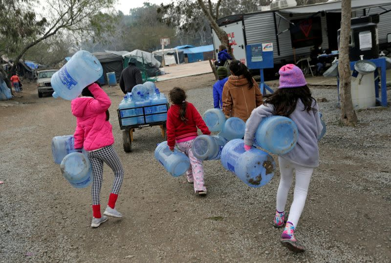 Children carry empty water containers inside a migrant encampment in Matamoros