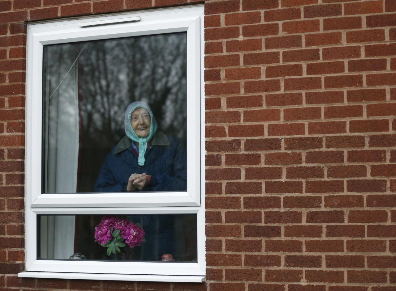 An elderly woman watches from the safety of her home as the hug passes. Shops boarded their windows and businesses closed early for the tense game (Reuters)