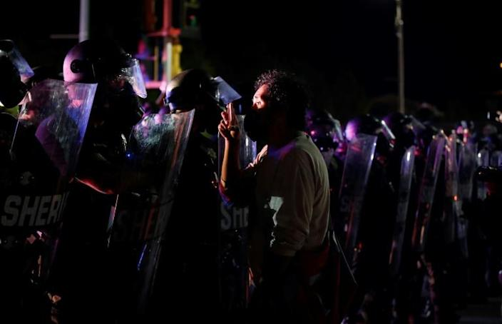 A protestor holds his cell phone as he faces off with sheriffs during demonstrations against the shooting of Jacob Blake in Kenosha, Wisconsin on August 25, 2020