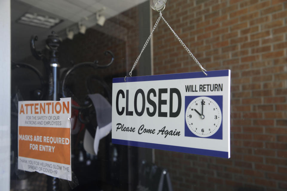 FILE - In this July 18, 2020 file photo a closed sign hangs in the window of a barber shop in Burbank, Calif. A critical snapshot of the job market and the economy to be released Friday, Oct. 2, is expected to show a further deceleration in hiring as the nation's viral caseload creeps higher just as financial aid from the government has faded. (AP Photo/Marcio Jose Sanchez, File)