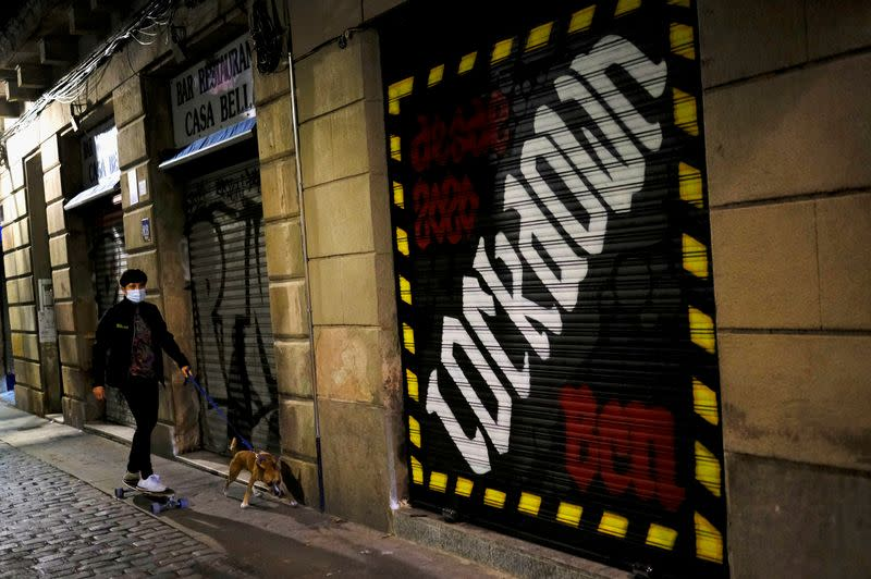 FILE PHOTO: FILE PHOTO: A woman is pictured with her dog in Barcelona, Spain, during an October lockdown to curb the spread of COVID-19