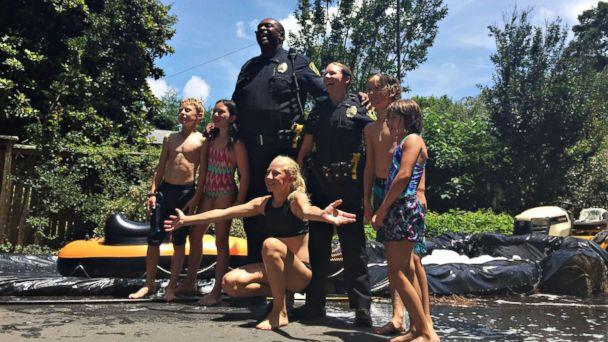 PHOTO: Children from the neighborhood pose with Asheville, North Carolina, police officers after riding down the slip 'n slide, July 2, 2017. (Courtesy of Travis Eagledove)