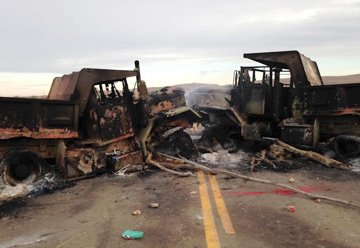 <p>The burned hulks of heavy trucks sit on Highway 1806 near Cannon Ball, N.D., on Friday, Oct. 28, near the spot where protesters of the Dakota Access pipeline were evicted from private property a day earlier. (Photo: James MacPherson/AP) </p>