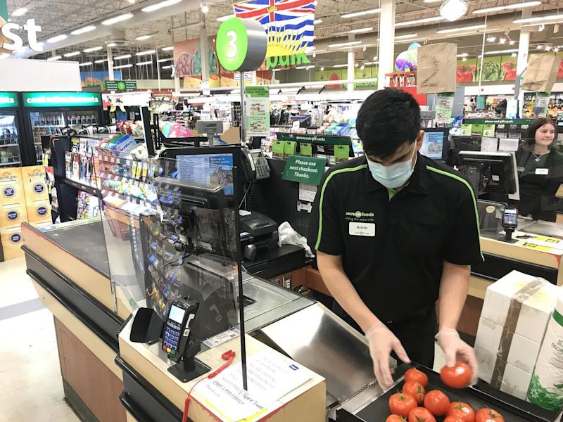 A grocery store cashier, wearing a mask and gloves, works behind a Plexiglas barrier.