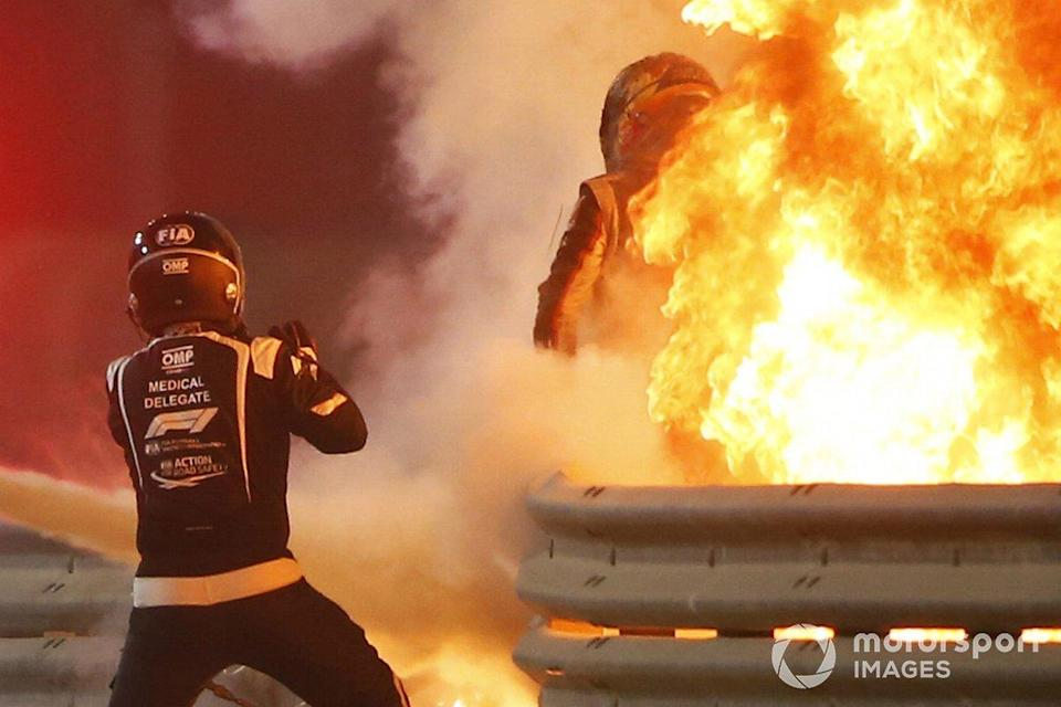 "Romain Grosjean, Haas F1, emerges from flames after a horrific accident on the opening lap of the Bahrain Grand Prix. Marshals extinguish the fire<span class=""copyright"">Andy Hone / Motorsport Images</span>"