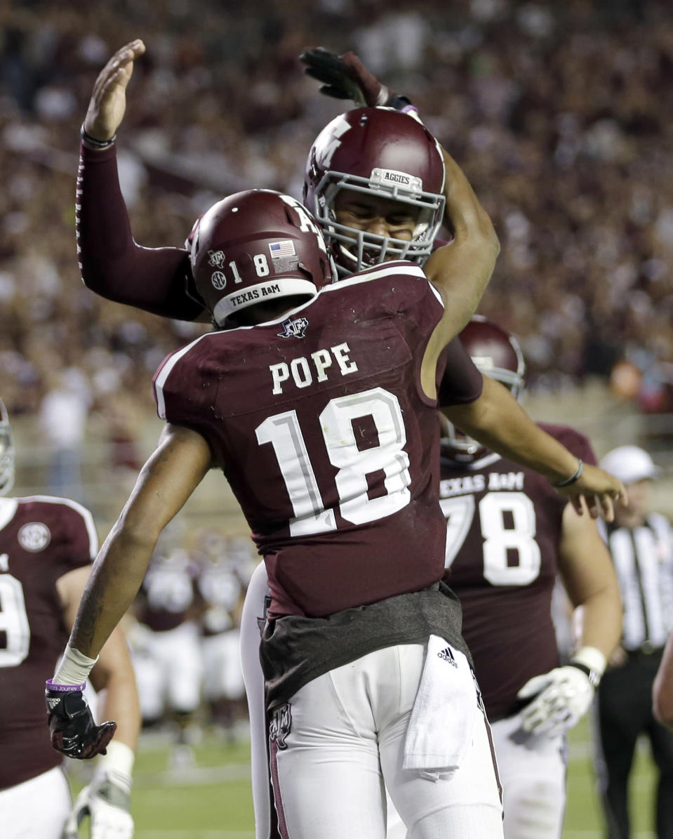 Texas A&M quarterback Kenny Hill, right, celebrates his touchdown pass to wide receiver Edward Pope (18) during the second quarter of an NCAA college football game against Lamar, Saturday, Sept. 6, 2014, in College Station, Texas. (AP Photo/David J. Phillip)