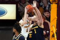 Minnesota's Liam Robbins (0) eyes the basket as Michigan's Hunter Dickinson (1) defends in the second half of an NCAA college basketball game, Saturday, Jan. 16, 2021, in Minneapolis. (AP Photo/Jim Mone)