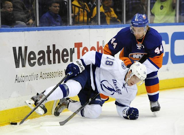 Tampa Bay Lightning Ondrej Palat (18) falls to ice trying to control the puck against New York Islanders' Calvin de Haan (44) in the first period of an NHL hockey game on Tuesday, Dec. 17, 2013, in Uniondale, N.Y. (AP Photo/Kathy Kmonicek)