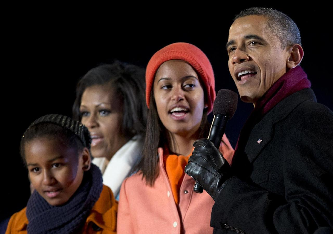 President Barack Obama, first lady Michelle Obama and their daughters Sasha and Malia, sing during the annual National Christmas Tree Lighting on the Ellipse, Thursday, Dec. 6, 2012, in Washington. This year's giant blue spruce is new, transplanted in October on the Ellipse, south of the White House. (AP Photo/Carolyn Kaster)