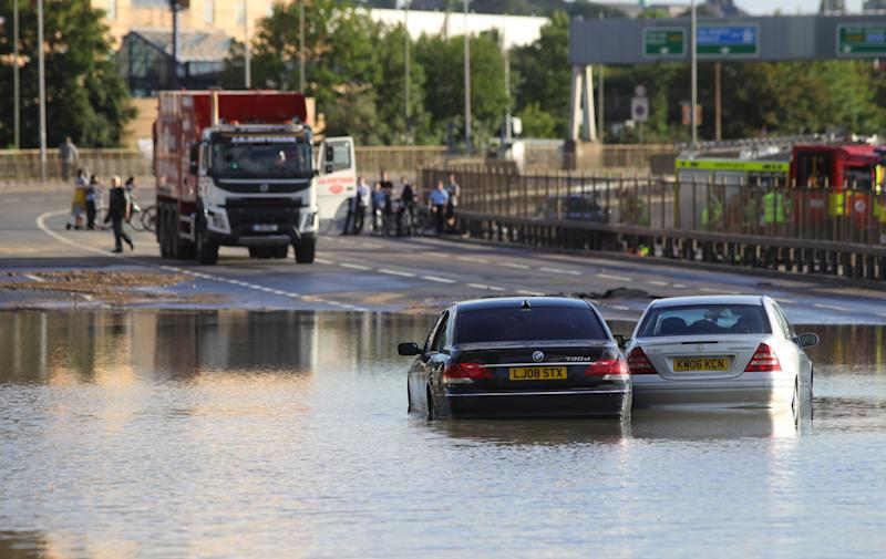 Abandoned cars in flood water on the North Circular road near Brent Cross, north London, after a water main burst. (Photo: PA)
